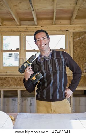 Man holding cordless drill at new construction site