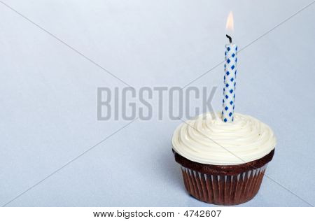 Chocolate Cupcake With Vanilla Frosting And A Candle