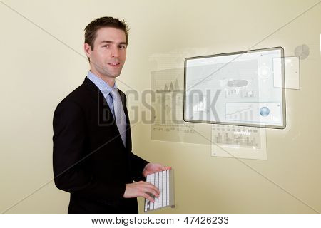 Portrait of young business man using a touch screen device with keyboard