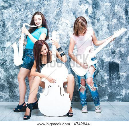 female rock band. girls with musical instruments: guitar, sax and cello
