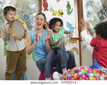 Young teacher with children playing music in classroom
