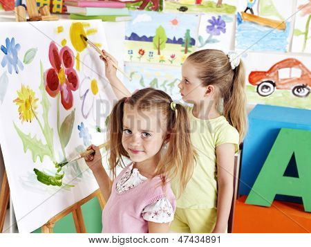 Children painting at easel in art class.
