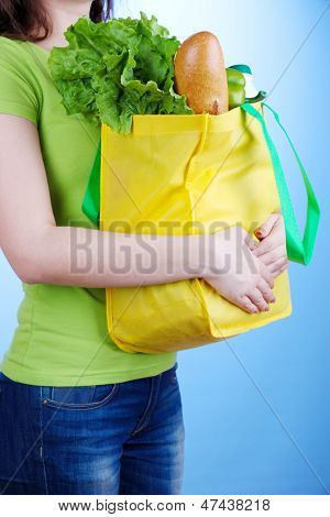 Girl with shopping bag on blue background
