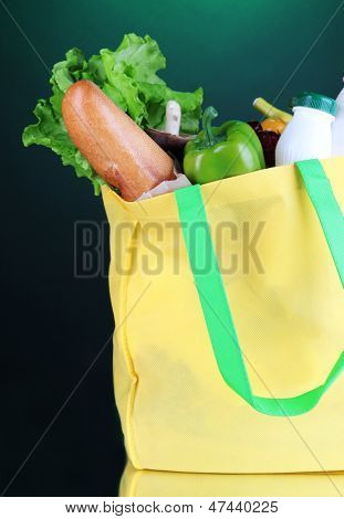 Eco bag with shopping on dark green background