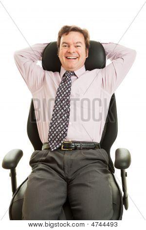 Executivo feliz em cadeira ergonómica