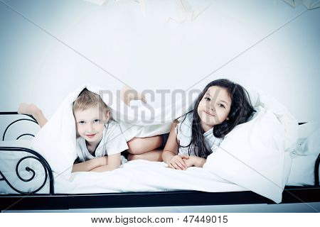 Cute kids lying together on the bed under the blanket. Dream world.
