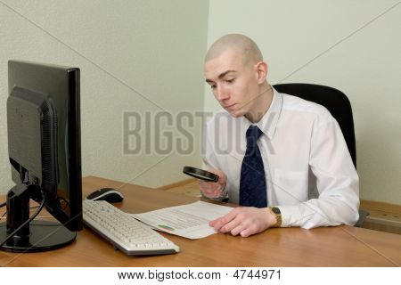 Businessman With A Magnifier On A Workplace
