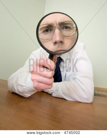 Man With A Magnifier In A Hand