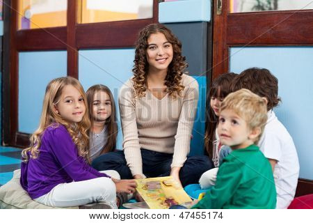 Portrait of young teacher and children with book sitting on floor in classroom