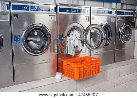 Washing machine overloaded with clothes and empty basket in laundry