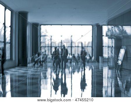 abstract image of a business people seating and walking in the lobby in intentional motion blur and a blue tint