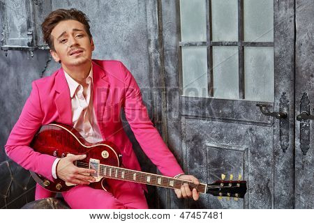 Young man in pink suit sits on armchair and plays semiacoustic guitar