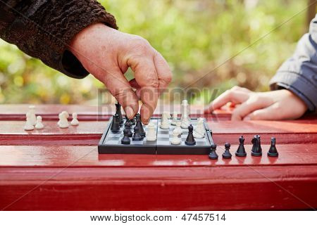 Grandmother hand makes move on chessboard in game in park outdoors, child hand lies on table in waiting