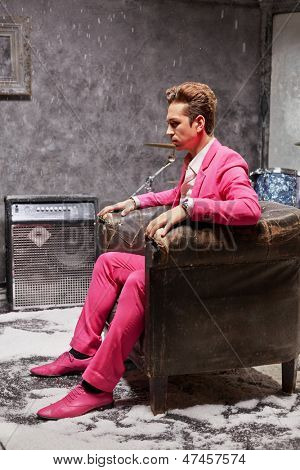 Profile portrait of young man in pink suit who sits motionlessly in old scuffed armchair and stares fixedly straight before himself