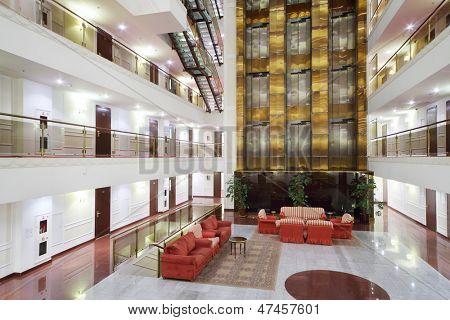 Atrium mit roten Sesseln, Sofas und Aufzüge in stilvollen Hotel.