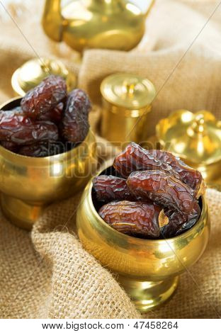 Dates. Dried date palm fruits or kurma, ramadan food which eaten in fasting month. Pile of fresh dried date fruits in golden metal bowl.