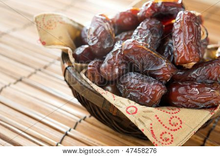 Dried date palm fruits or kurma, ramadan food which eaten in fasting month. Pile of fresh dried date fruits ready to eat in bamboo basket.