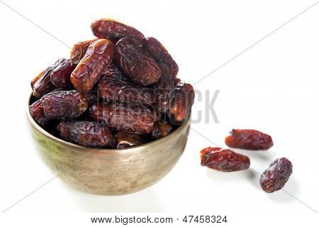 Dates fruit.  Kurma dried date palm fruits, Ramadan food which eaten in fasting month for Muslim. Pile of fresh dried date fruits in a bowl.