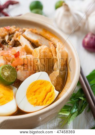 Prawn noodles or prawn mee. Famous Singapore food spicy fresh cooked har mee in clay pot with hot steam. Asian cuisine.