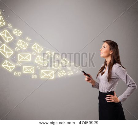 attractive young lady standing and holding a phone with message icons