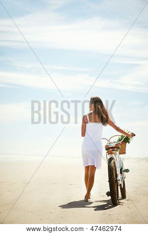 Woman walking with bicycle along beach sand summer lifestyle carefree
