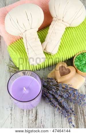 Still life with lavender candle, soap, massage balls, soap and fresh lavender, on wooden background