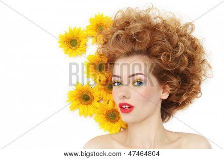Joven mujer sexy feliz hermosa con el pelo rizado y girasoles sobre fondo blanco