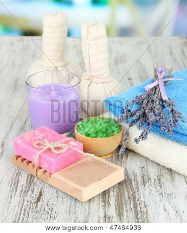 Still life with lavender candle, soap, massage balls, bottles,  soap and fresh lavender, on wooden  table on bright background