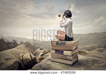beautiful woman sitting on a pile of old books watching with binoculars