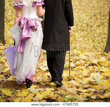 Gentlemen and ladies are on the autumn leaves.
