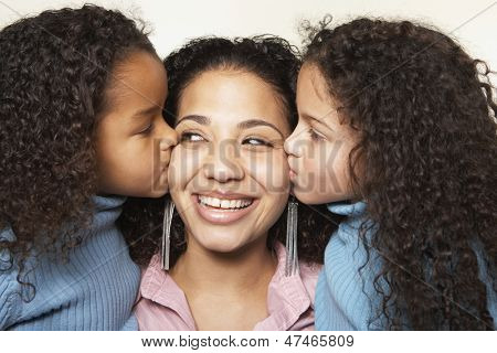 Girls kissing mother on cheek