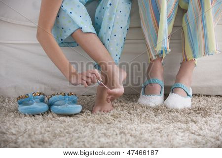 Close up of young girl painting her toenails