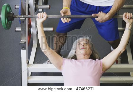 Personal trainer with female client lifting weights