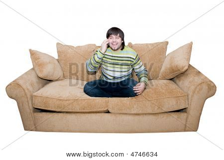 Happy Young Man Talking And Smiling On The Cell Phone Sitting On The Sofa