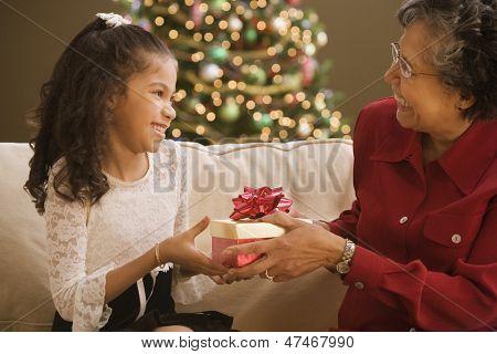 Grandmother giving granddaughter Christmas gift
