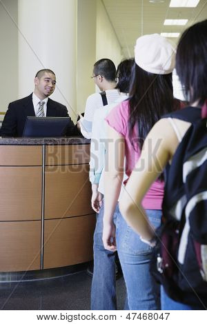 Man sitting at reception desk with people standing  in a queue