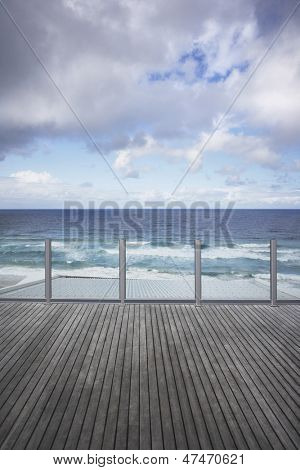 Wooden dock overlooking ocean against cloudy sky