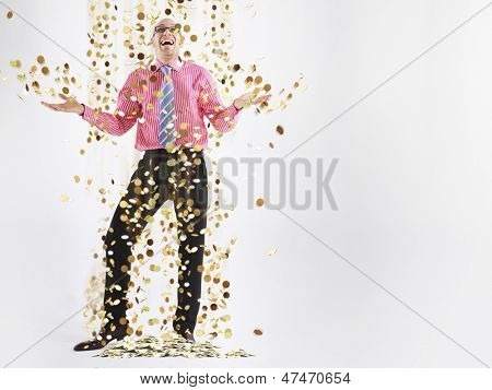 Full length of a happy male executive under shower of gold coins against white background