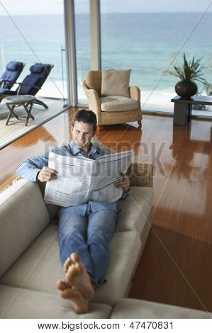 Full length of happy young man reading newspaper on sofa