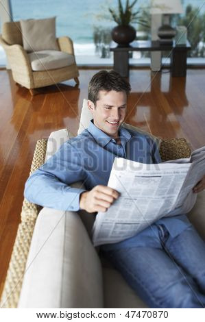 Happy young man reading newspaper on sofa at home