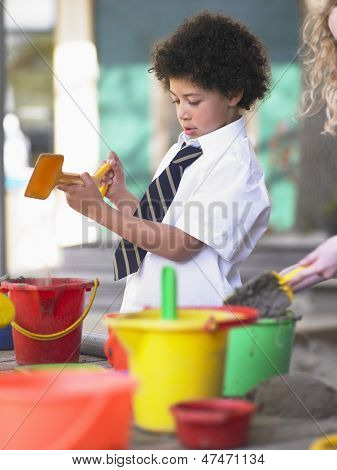 Elementary schoolboy playing in sand pit in school playground