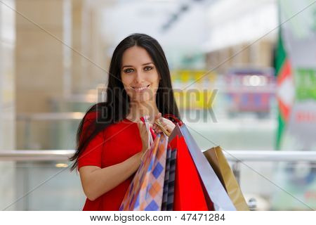 Young Woman Shopping in Mall Holding Paper Bags