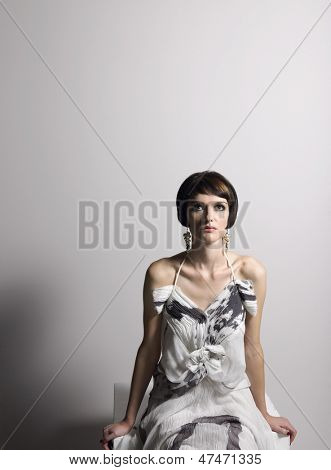 Serious young woman in dress sitting against gray background