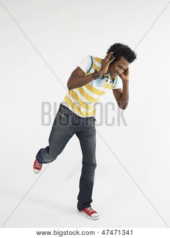 Afro young man dancing while wearing headphones against white background
