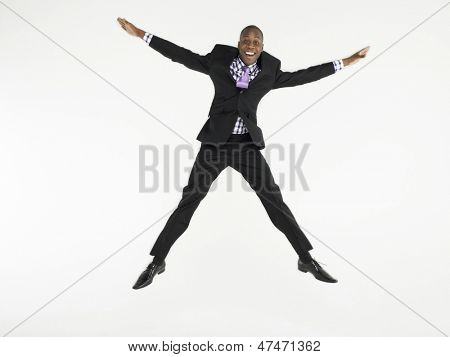 Full length portrait of a bald businessman jumping in star shape against white background