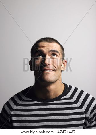 Smiling young man in striped tshirt looking up against gray background