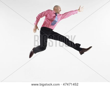 Full length of a bald businessman jumping against white background
