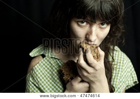 portrait of a poor beggar woman eating bread