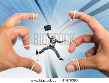 Stressed businessman governed by puppeteer hands