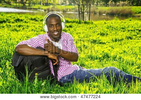 Smiling young african american man  with rucksack listens music in a park